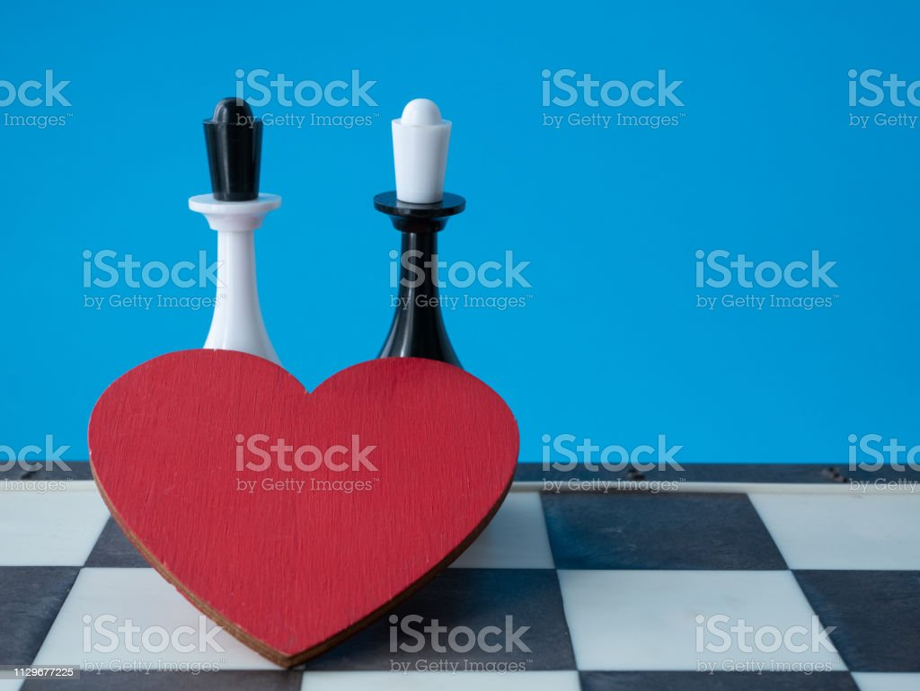 love between two woman lgbt couple concept. two chessman queens with red hear on blue background. lesbian wedding invitation