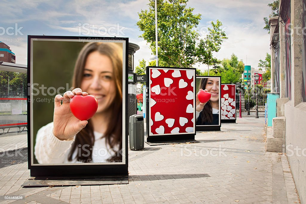 Love billboards, photographs of a woman with red heart Love billboards, photographs of a woman with red heart, at city street in valentine´s day Adult Stock Photo