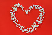 istock Love cinema concept of popcorn. Heart shaped white fluffy popcorn on red background with empty space for text 1203256566
