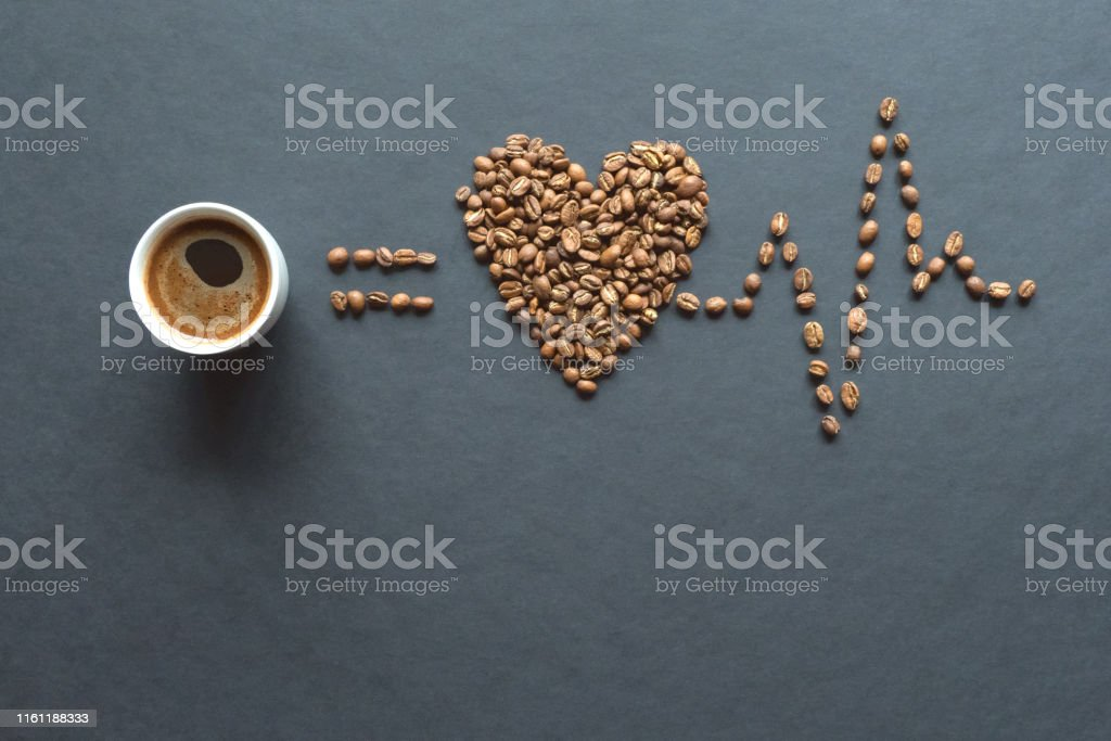 Love coffee concept. Heart from roasted coffee beans and cup of...