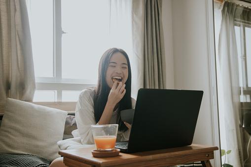 Young Thai woman Enjoy watching the movie at home, Bangkok Thailand