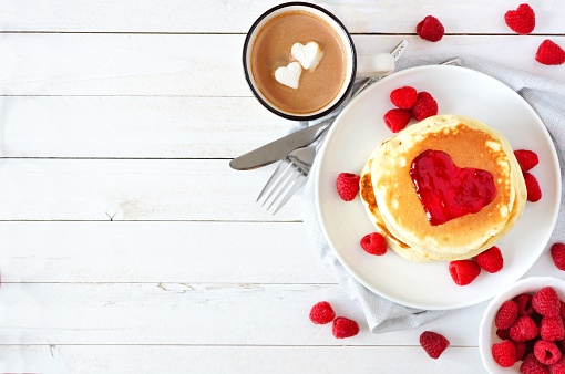 Love concept breakfast with pancakes, hot chocolate and raspberries over white wood