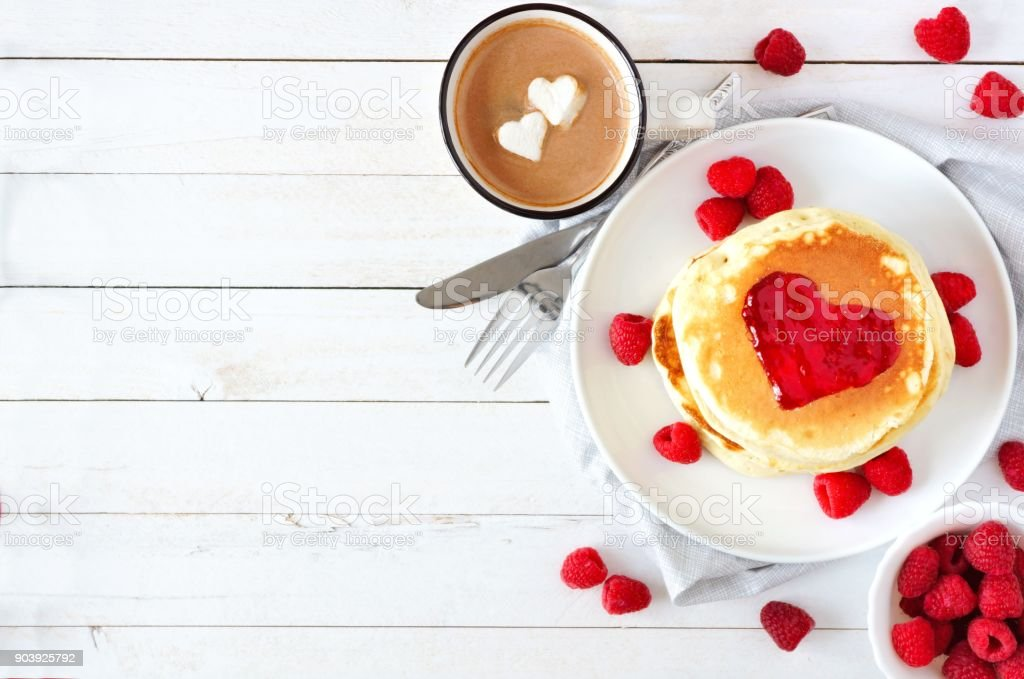 Love concept breakfast with pancakes, hot chocolate and raspberries over white wood stock photo