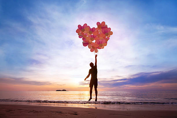love concept love concept, man flying with heart from balloons, fall in love love at first sight stock pictures, royalty-free photos & images