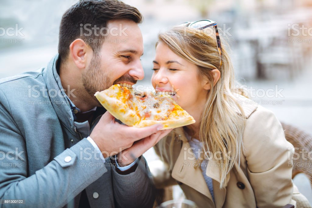 Love couple in a restaurant eating pizza. stock photo