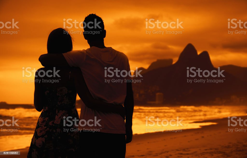 Love couple in arms on beach at sunset at Rio ストックフォト