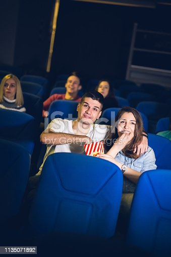 187095683 istock photo Love couple in the cinema watching a movie. 1135071892