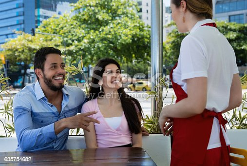 635812444 istock photo Love couple place an order at a caucasian waitress 635754682