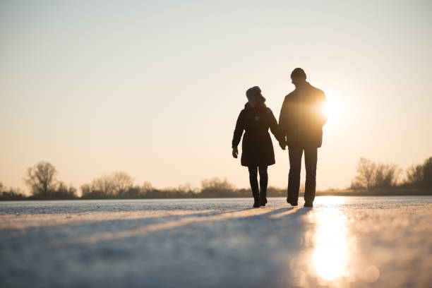 Love couple walking while holding hands stock photo
