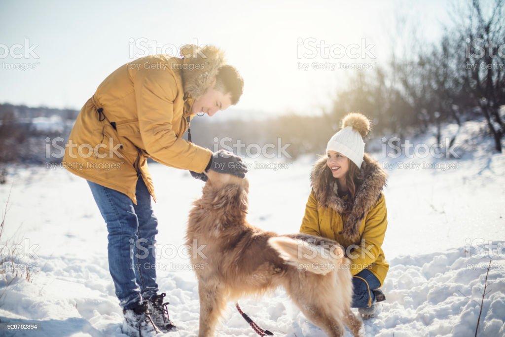 Liebespaar mit Hund haben Spaß im Schnee – Foto