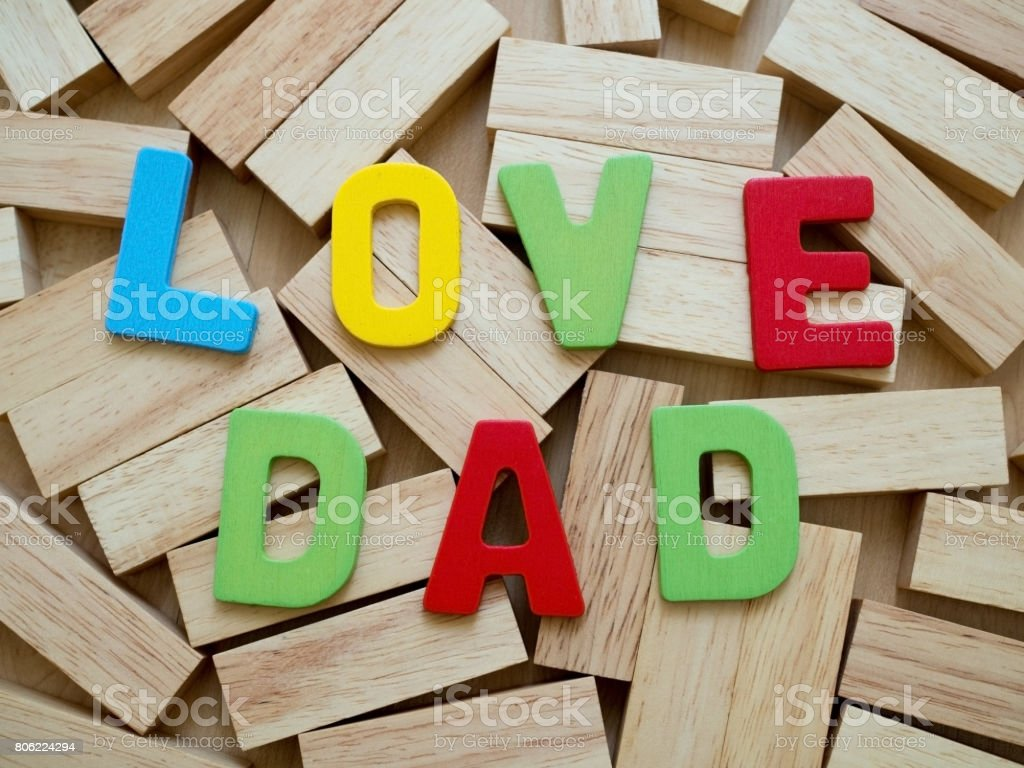 Love dad. Happy Father's Day celebrations. Love dad word from colorful of wood on wooden block in background. Father's day. stock photo