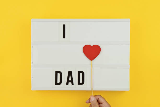 I love Dad text on white lightbox with wooden heart on yellow background stock photo