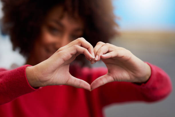 Love everything Cropped shot of an unrecognizable woman forming a heart shape with her fingers amor stock pictures, royalty-free photos & images