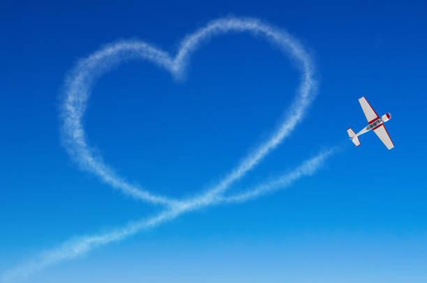 figurative herz aus einem weißen rauchfahne flugzeug - schrift am himmel stock-fotos und bilder
