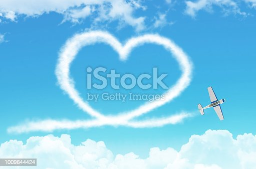 istock Love figurative heart from a white smoke trail light-engine airplane among the clouds. 1009644424