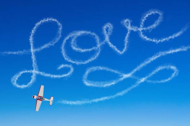 liebe figurative inschrift aus einem weißen rauchfahne flugzeug - schrift am himmel stock-fotos und bilder