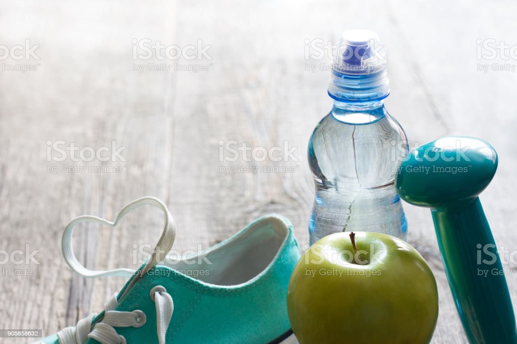 Love fitness and diet abstract background concept with heart shoelace and gym equipment stock photo
