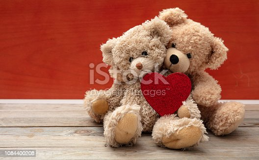 istock Love, friendship concept, tight hug. Teddy bears couple on wooden floor, red wall background 1084400208