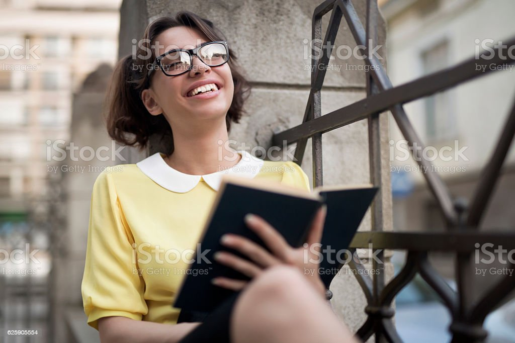 Cute, caucasian young woman leaning on the fence, reading and laughing