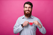 istock I love. Handsome bearded man is holding a heart shaped paper on his chest on pink background. 1160180565