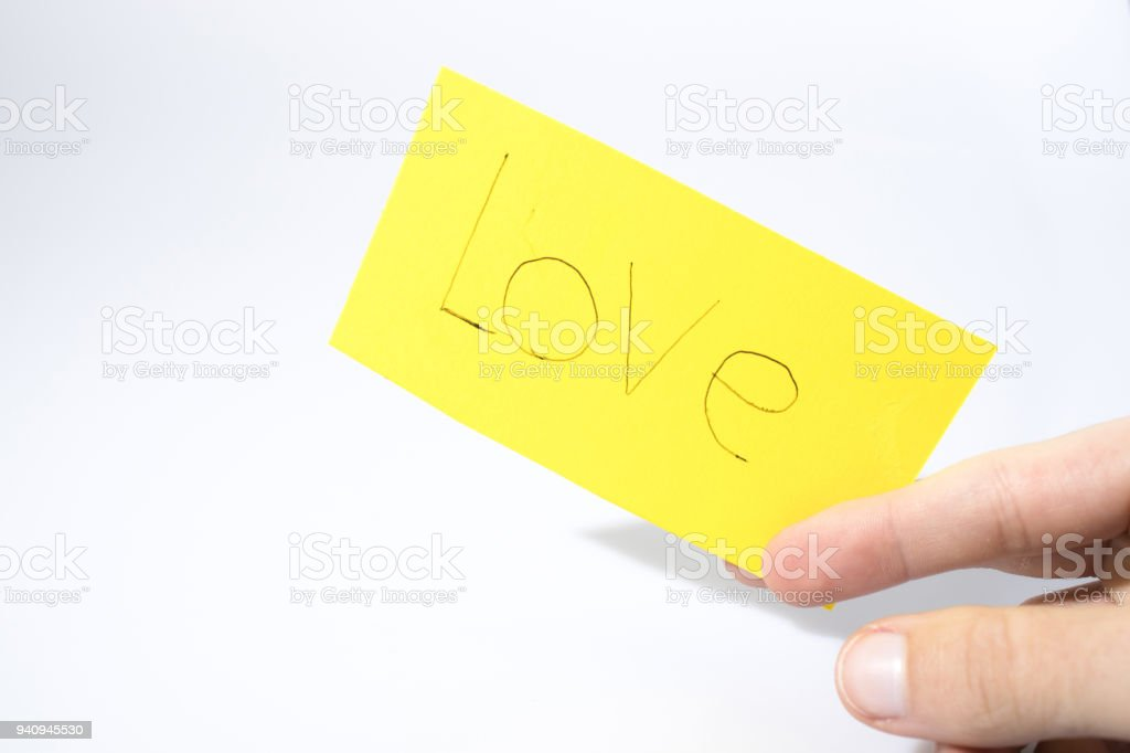 Love handwrite with a hand on a yellow paper compsoition stock photo