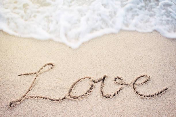Love handwritten on the beach stock photo