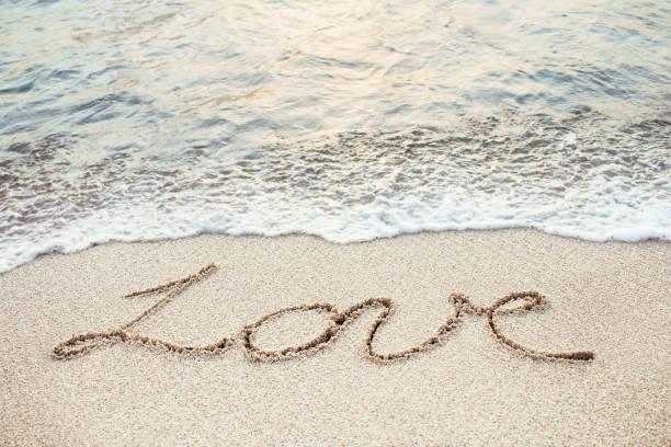 Love handwrittten on the tropical beach stock photo