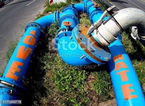 Mixing emotional flows: the picture of a city gas pipeline used to depict interconnection between 2 opposite emotional states: love and hate. Both extreme and still connected. The shot has been taken in , metaphor. Berlin, Germany - August 4, 2019.  Blue gas city pipeline. Text over the pipes is a digital enhancement added by myself