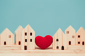 istock Love heart between two house wood model for stay at home for healthy community together concept. 1219495163