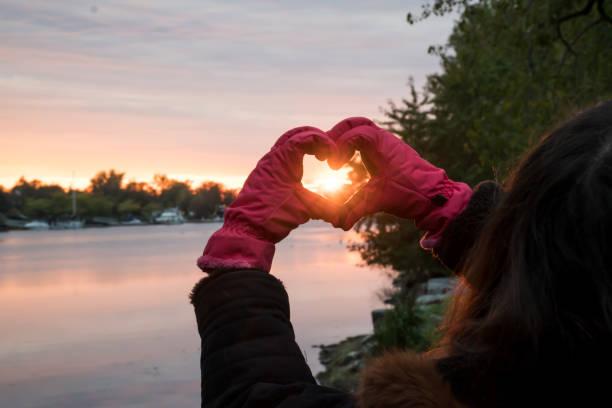 Love - Heart Shape Hands beautiful Sunset Winter Solstice Landscape over water stock photo