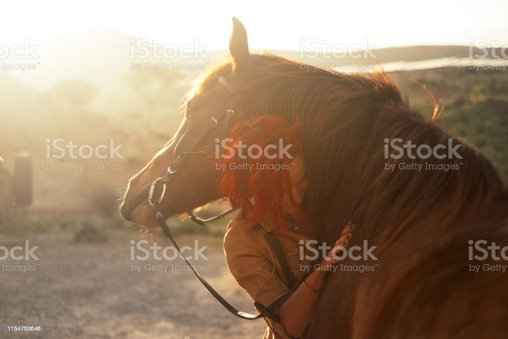 Love horse animal pet therapy red hair young pretty woman hug with...