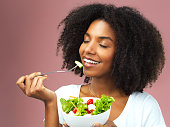 Studio shot of an attractive young woman eating salad against a pink background