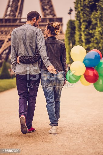 Photo of smiling, loving couple enjoying together in the city of love, Paris. Man is holding colourful balloons.