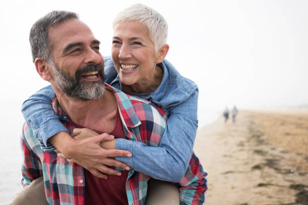 Love is always playful Mature playful couple at beach 55 59 years stock pictures, royalty-free photos & images
