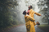 Carefree woman having fun while being held by her boyfriend on a rain in nature. Copy space.