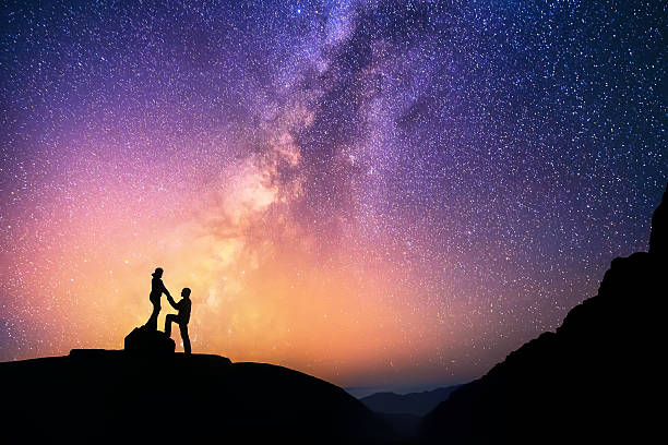 Love is in the air Romantic couple standing together holding hands in the mountains. Beautiful Milky Way galaxy on the background. romance stock pictures, royalty-free photos & images