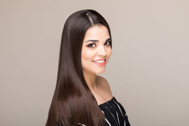 Love Is In The Hair Smiling Hispanic woman with beautiful hair and skin over colored background straight hair stock pictures, royalty-free photos & images