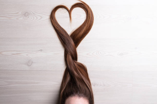 love is in the hair long hair forming a tress ending with a shape of heart long hair stock pictures, royalty-free photos & images