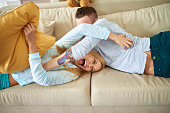 Carefree couple tickling each other lying on sofa