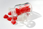 Old glass bottle with red heart shape gummy spilling on white background