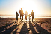 Rearview shot of a happy young family bonding on the beach at sunset