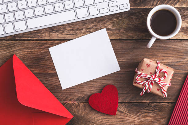 love letter, envelope, keyboard, coffee,  small gift on wooden table. - filzunterlage stock-fotos und bilder