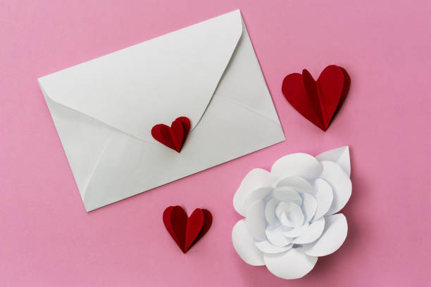 Love letter envelope with red paper hearts and white flowers. stock photo