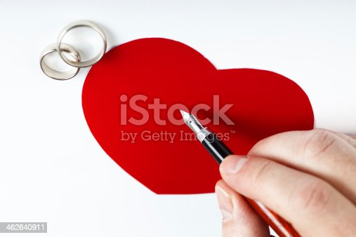 Man writing on red paper heart with two wedding rings