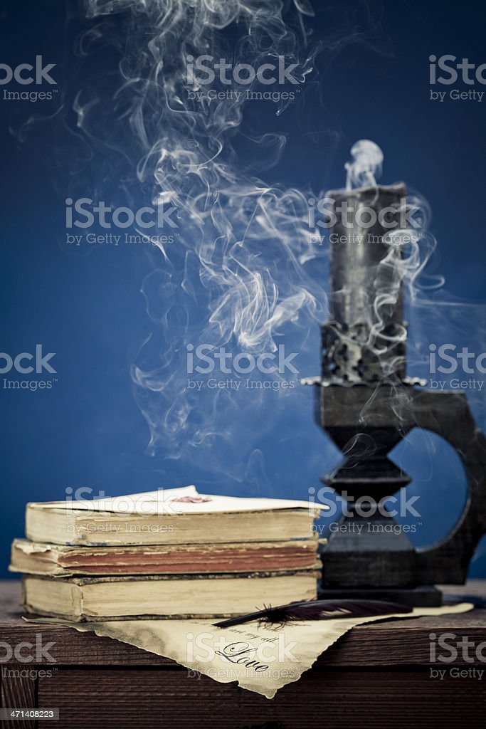 love letter with old books and blown out candle stock photo