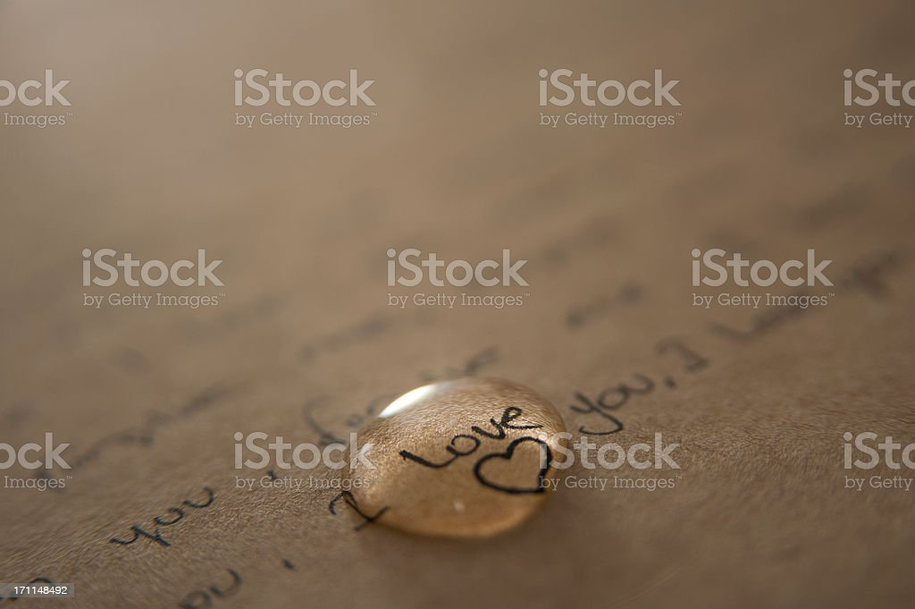 A love letter written on brown paper with a gold love heart  stock photo