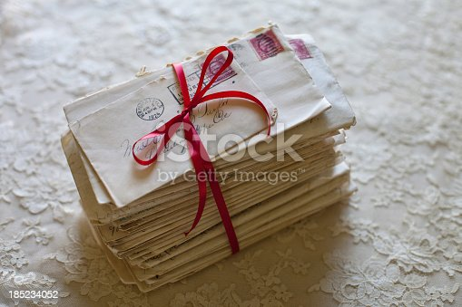Stack of old letters tied in red ribbon
