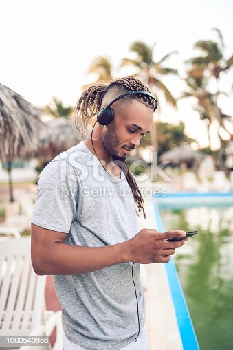 Latin Male With Dreadlocks Listening Music On Mobile Phone On Cuban Beach Resort