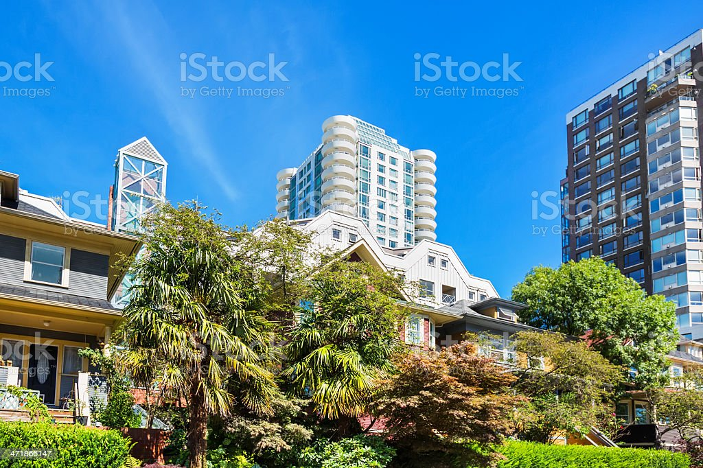 Homes and apartment buildings in Vancouver. Shrubbery and trees line...
