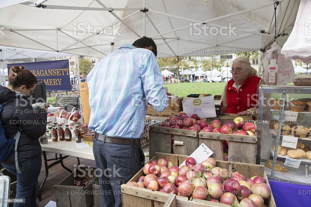 People are purchasing fruits and vegetables at an open air market in...